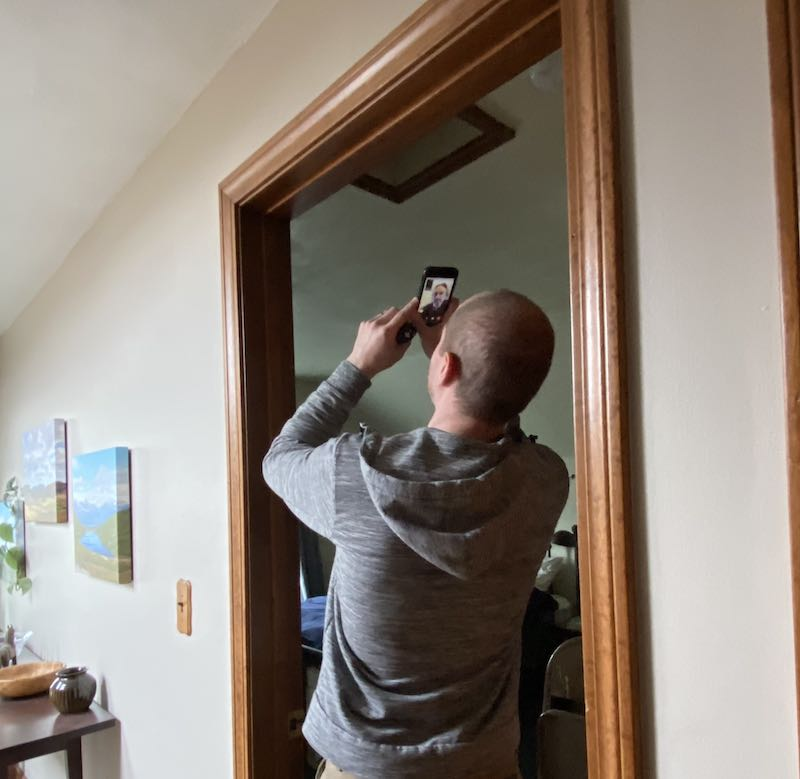 Person looking at their attic hatch with a phone, conducting a video call for a virtual energy audit
